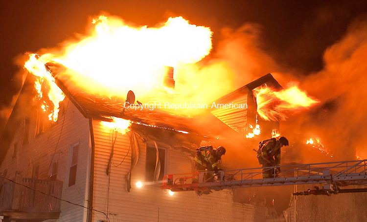 WATERBURY, CT 22 DECEMBER- 122212JS07- A pair of Waterbury firefighters make their way down the ladder as the the signal to exit the building while battling a structure fire Saturday night at a multi-family home at 27 West Porter Street in Waterbury..Jim Shannon Republican American