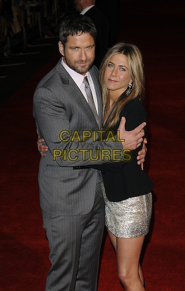 GERARD BUTLER & JENNIFER ANISTON .Attending 'The Bounty Hunter'  UK film premiere at the Vue West End,cinema Leicester Square, London, England, UK,.11th March 2010.arrivals half length grey gray pinstripe suit arm around smiling black jacket silver beaded shiny metallic dress tux tuxedo beard facial hair  hand ring arms hug hugging .CAP/CAN.©Can Nguyen/Capital Pictures