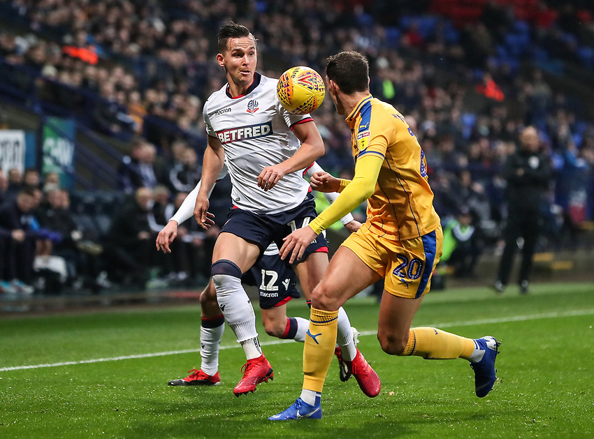Bolton Wanderers' Pawel Olkowski competing with Wigan Athletic's Kal Naismith<br /> <br /> Photographer Andrew Kearns/CameraSport<br /> <br /> The EFL Sky Bet Championship - Bolton Wanderers v Wigan Athletic - Saturday 1st December 2018 - University of Bolton Stadium - Bolton<br /> <br /> World Copyright © 2018 CameraSport. All rights reserved. 43 Linden Ave. Countesthorpe. Leicester. England. LE8 5PG - Tel: +44 (0) 116 277 4147 - admin@camerasport.com - www.camerasport.com
