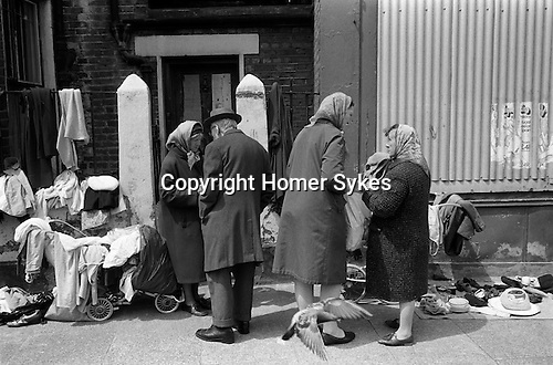 Woman selling old clothes from a pram  Whitechapel  near Brick Lane. East London  1972. pigeon flying up.<br />