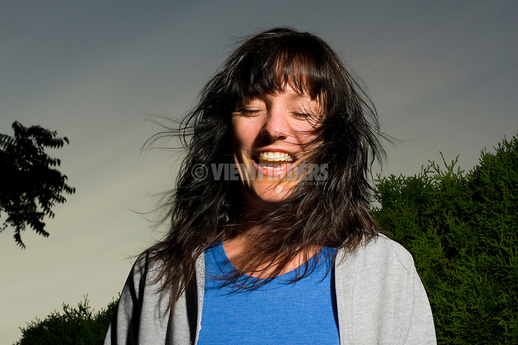 Woman Shaking Head and Laughing at Dusk