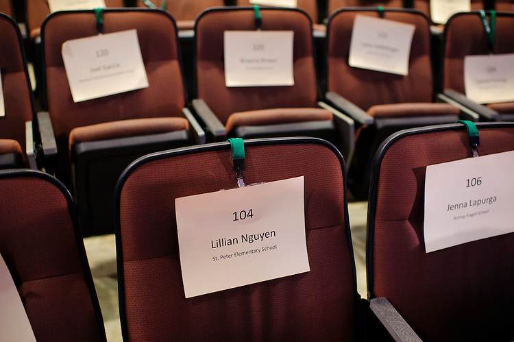Official Regional Bee name tags are draped over chairs to reserve the participants seating during a 10-minute break between spelling rounds Saturday, March 16, 2013.