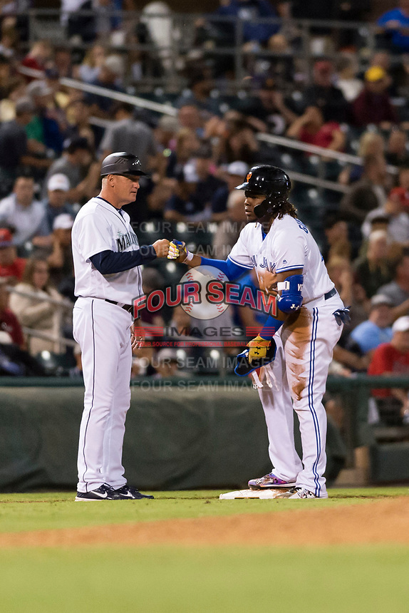 AFL West third baseman Vladimir Guerrero Jr. (27), of the Surprise Saguaros and Toronto Blue Jays organization, is congratulated by manager Daren Brown (43) during the Arizona Fall League Fall Stars game at Surprise Stadium on November 3, 2018 in Surprise, Arizona. The AFL West defeated the AFL East 7-6 . (Zachary Lucy/Four Seam Images)