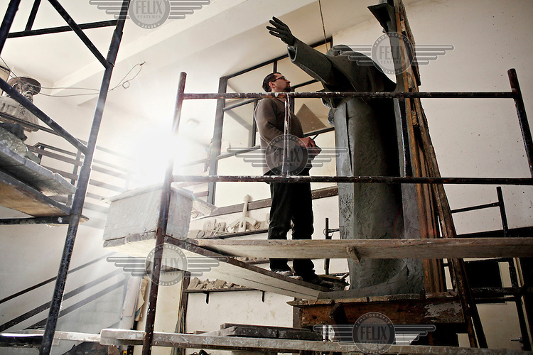 An artist at Czeslaw Dzwigaj sculptor workshop scupting a statue of Pope John Paul II. Dzwigaj has made over 70 sculptures of the late pope.