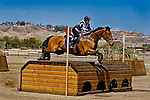 Women jumping her horse over a table top jump in the cross country event for the FCI World Cup of 3 Day Eventing held at Galway Downs Equestrian Center in Temecula California.