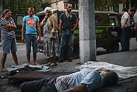 People watch a civilian killed by shrapnel from shelling on the street of Donetsk, Eastern Ukraine.