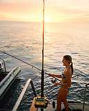 FIJI, Northern Lau Islands, a young woman fishes from the back of a yatch