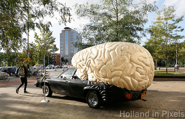 Nederland  Amsterdam  2016 . De Braincar van Olaf Mooij. De Braincar is een auto waarvan de bovenkap is omgevormd tot grote hersenpan. Overdag rijdt de auto door een wijk, stad of straat, en in de avond droomt de auto van zijn dag door middel van videoprojecties op het matwitte hersenvlak.  Foto Berlinda van Dam / Hollandse Hoogte