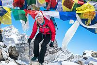 A woman ducks beneath prayer flags on the top of Gokyo Ri, 5356. meters, a popular hiking peak in the Nepal Himalaya.