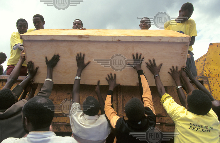©Paul Lowe/Panos Pictures..Kigali, RWANDA   6/4/1995..Offloading a crate containing the bones of 300 victims of the genocide..Hundreds gathered on the Rebero hills near Kigali in a memorial ceremony for the thousands of Tutsis killed in the genocide war between Tutsis and Hutus in 1994. Trucks brought massive wooden crates, a total of around 200 which contained the skulls and bones of 6000 people murdered in and around the main hospital of Kigali.