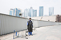 Qatar - Doha - An Indian worker standing in a street of West Bay,  a newly developed neighborhood of Doha. It is considered as one of the most prominent districts of Doha, being the latest district to be built. West Bay includes many modern buildings unlike other, older districts of Doha. Some of the tallest skyscrapers in Qatar are found in this area.
