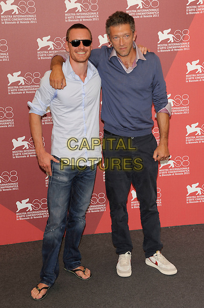 Michael Fassbender & Vincent Cassel .Attending the 'A Dangerous Method' photocall at the Palazzo del Casino during the 68th Venice Film Festival, Venice, Italy, September 2nd 2011..full length blue jumper sweater shirt v-neck nike white trainers  navy trousers arm around sunglasses jeans shirt flip flops .CAP/PL.©Phil Loftus/Capital Pictures.