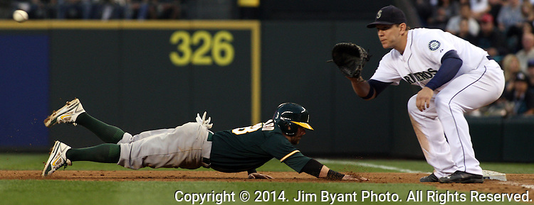 Oakland Athletics  Coco Crisp slides safely back to first as Seattle Mariners Logan Morrison awaits the throw September 13, 2014 at Safeco Field in Seattle.The Athletics beat the Mariners 3-2 when Mariners pitcher Fernando Rodney  walked in Coco Crisp in the 10th inning.  ©2014. Jim Bryant Photo. All Rights Reserved.