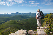 A hiker takes in the view of the Pemigewasset Wilderness from the summit of Zeacliff during the summer months. This viewpoint is located along the Appalachian Trail in the New Hampshire White Mountains USA.