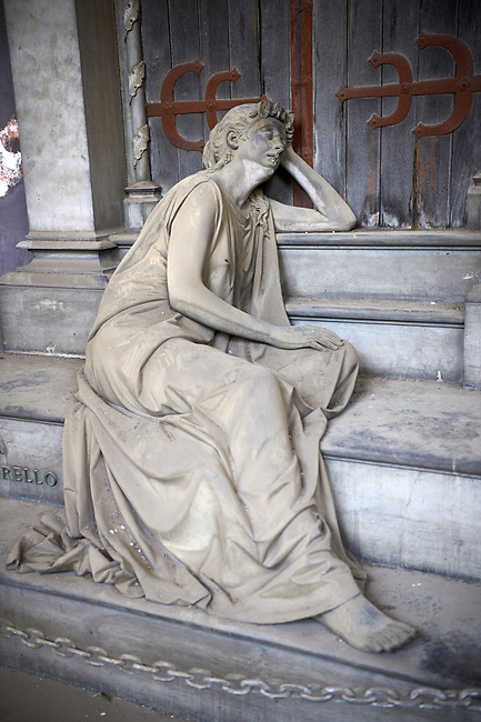 Pictures and image of the stone sculpture of a mouring widow sitting on the steps of the tomb. The Lavarello Family Tomb sculpted by S Saccomanno 1890. Section D no 32, the monumental tombs of the Staglieno Monumental Cemetery, Genoa, Italy