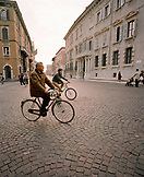 ITALY, Verona, people riding bicycles on street with buildings in the background