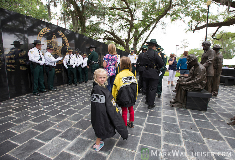 Five year old Alaina Crews, center left, looks over her shoulder as her 8 year old sister Kinley Crews watches her mother take photos of the Nassau County Sheriffs after the Florida Sheriffs Association 2017 Law Enforcement Memorial Ceremony at the Florida Sheriffs Association in Tallahassee, Florida.
