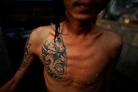 A HIV-positive patient with a devil tattoo on his chest baths at the at the HIV/AIDS hospice, founded by a member of the National League for Democracy (NLD) party in suburbs of Yangon May 26, 2012.   REUTERS/Damir Sagolj (MYANMAR)