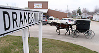 A horse and buggy travels past a row of cars outside a business in Drakesville in southeast Iowa's Davis County.   It is among only a handful of rural Iowa counties in the 2010 Census to gain population (2.4 percent).  Much of that population growth is due to a steadily growing Amish population.  (Christopher Gannon/The Des Moines Register)