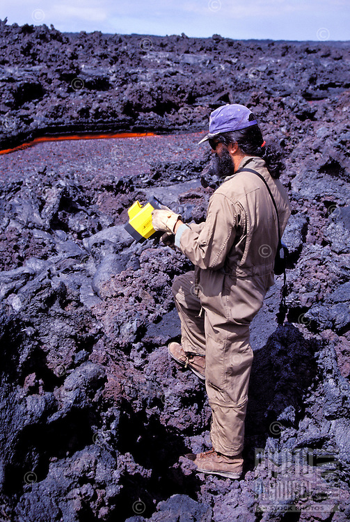 Volcanologist measuring lava flow from Kilauea, the worlds most active volcano