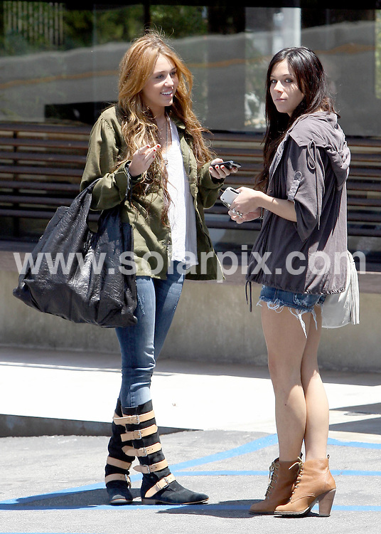 **ALL ROUND PICTURES FROM SOLARPIX.COM**.**SYNDICATION RIGHTS FOR UK AND SPAIN ONLY**.Miley Cyrus shows off her funky boots to her friend in Toluca Lake, San Fernando Valley, Los Angeles, California, USA. 23 May 2010..This pic: Miley Cyrus..JOB REF: 11313 STL        DATE: 23_05_2010.**MUST CREDIT SOLARPIX.COM OR DOUBLE FEE WILL BE CHARGED**.**MUST NOTIFY SOLARPIX OF ONLINE USAGE**.**CALL US ON: +34 952 811 768 or LOW RATE FROM UK 0844 617 7637**