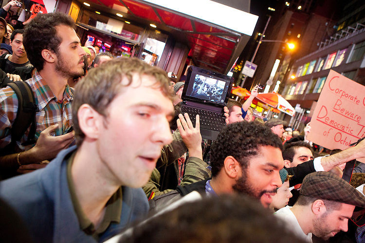 """Protesters with """"Occupy Wall Street"""" are blocked by barricades in Times Square on October 15, 2011 in New York City but that does not stop them from streaming the confrontation live online.  While crowd estimates numbered in the tens of thousands, police tactics (including nets, motor scooters, barricades, arrests, and intimidation by riders on horseback) prevented the crowd, which had been split up, from joining together as one in the middle of Times Square."""