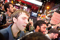 "Protesters with ""Occupy Wall Street"" are blocked by barricades in Times Square on October 15, 2011 in New York City but that does not stop them from streaming the confrontation live online.  While crowd estimates numbered in the tens of thousands, police tactics (including nets, motor scooters, barricades, arrests, and intimidation by riders on horseback) prevented the crowd, which had been split up, from joining together as one in the middle of Times Square."