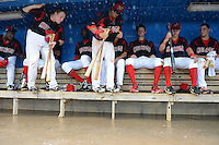 Batavia Muckdogs catcher Chad Wallach (55) and infielder Avery Romero (13) work their way down the dugout after it flooded during a brief but heavy rain storm during a game against the Hudson Valley Renegades on August 8, 2013 at Dwyer Stadium in Batavia, New York.   Looking on is Javier Lopez, J.T. Riddle, Justin Bohn, and Austin Dean;  the game was called due to unplayable field conditions.  (Mike Janes/Four Seam Images)