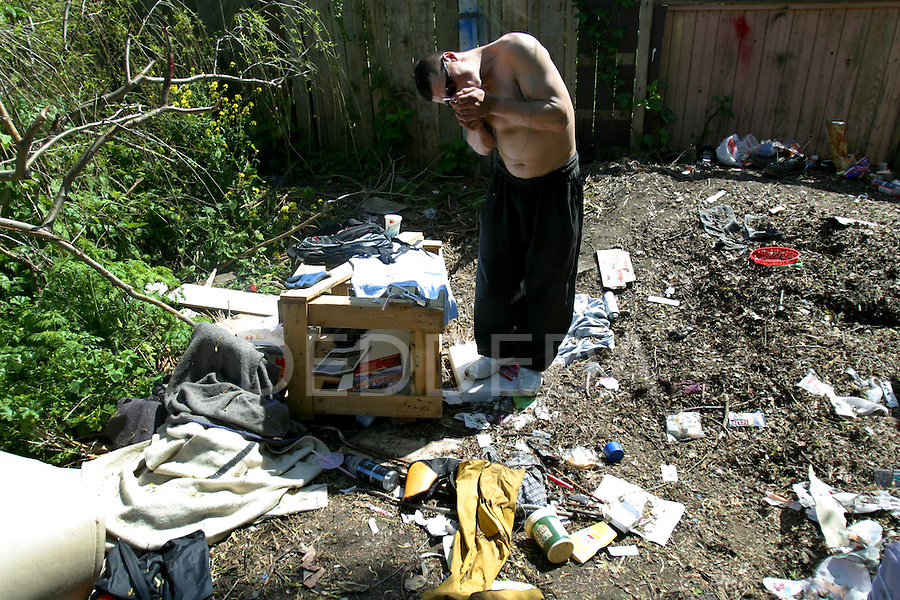 A drug addict named Kei, 29, heats his fix of morphine mixed with cocaine and synthetic heroin before injecting it into his arm in a vacant lot along Mason Street in Victoria, B.C. The vacant lot, littered with garbage and used needles, is a common site for intravenous drug users to utilize as a shooting gallery. Photo shot for the GLOBE and MAIL.