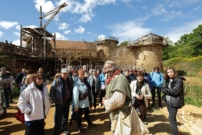 Tour guide and miller Yohann Mateo Albaladejo, dressed in medieval costume, taking visitors on a guided tour at the Chateau de Guedelon, a castle built since 1997 using only medieval materials and processes, photographed in 2017, in Treigny, Yonne, Burgundy, France. The Guedelon project was begun in 1997 by Michel Guyot, owner of the nearby Chateau de Saint-Fargeau, with architect Jacques Moulin. It is an educational and scientific project with the aim of understanding medieval building techniques and the chateau should be completed in the 2020s. Picture by Manuel Cohen