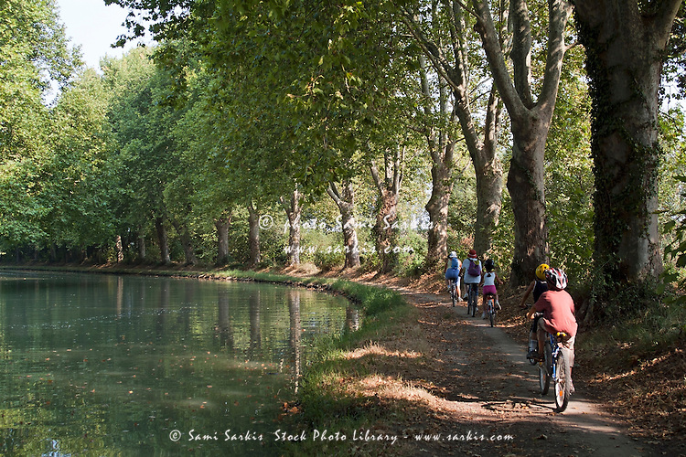 Family cycling near a canal, Canal du Midi, Carcassonne, France.