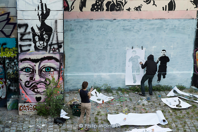 A street artist wearing a hoodie (name unknown) uses stencils to create a mural of children attacked by a drone in the style of Banksy on a wall bordering a well-used footpath along the Danube Canal, Vienna.