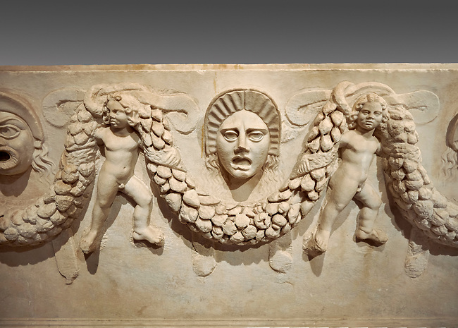 """Close up picture of Roman relief sculpted Sarcophagus of Garlands, 2nd century AD, Perge. This type of sarcophagus is described as a """"Pamphylia Type Sarcophagus"""". It is known that these sarcophagi garlanded tombs originated in Perge and manufactured in the sculptural workshops of Perge. Antalya Archaeology Museum, Turkey.. Against a grey background."""