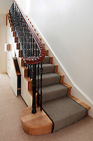 A traditional style staircase with a striped stair carpet. The staircase has decorative wrought iron spindles and a wooden banister. A cupboard built under the stairs provides extra storage.