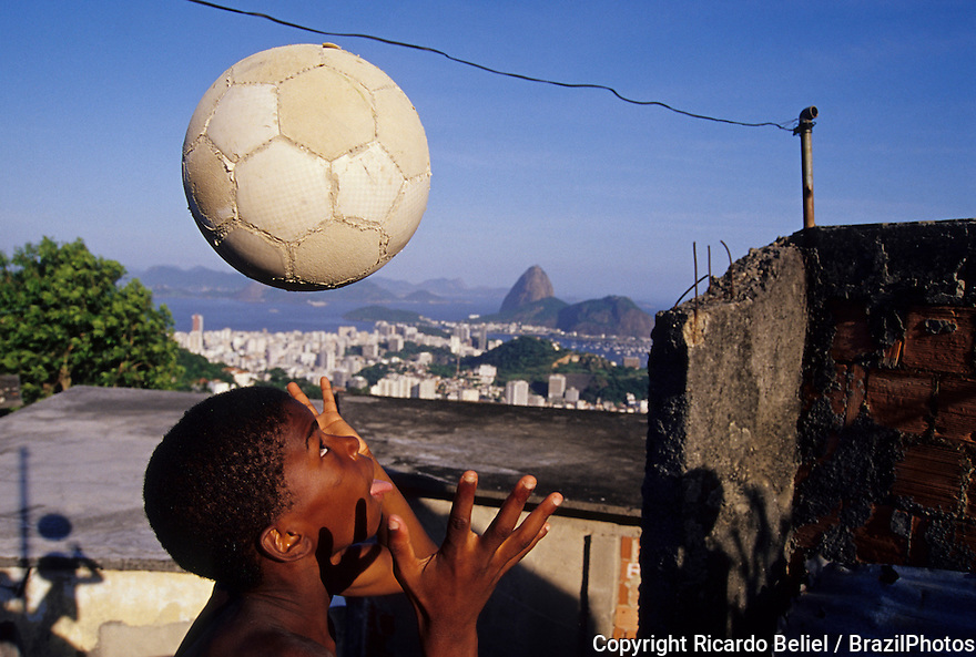 Child plays soccer in a Rio de Janeiro favela, black boy have fun with his ball, Sugar Loaf mountain in background.