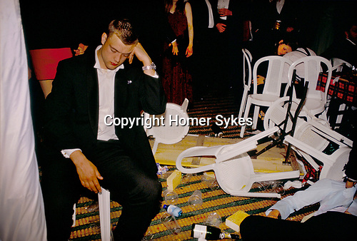 DRUNKEN REVELLERS SITTING & LYING AMONGST TRASHED FURNITURE AT THE ROYAL AGRICULTURAL COLLEGE MAY BALL, CIRENCESTER, GLOS,
