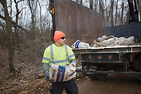 Merced Cervantes, environmental officer, carries a discarded bag of Hydaul-EZ borehole stabilizer, Monday, February 10, 2020 along Logan Cave Rd. in Siloam Springs. Check out nwaonline.com/200211Daily/ for today's photo gallery.<br /> (NWA Democrat-Gazette/Charlie Kaijo)<br /> <br /> A cleanup crew from the Environmental Division for Benton County Government picked up illegally discarded waste products. <br /> <br /> Teresa Sidwell, environmental manager, said a lot of times people are trying to avoid having to pay to take it to the land fill, but added, they have a program where people can drop off large waster products for free.
