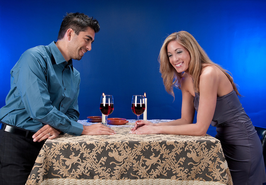 Couple drinking wine and having fun in night club or restaurant setting. Male model young in his 20's with mature woman in her 40s.