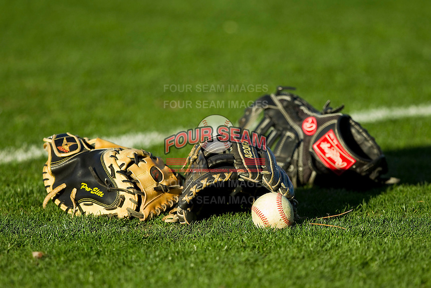 Baseball gloves and a baseball sit on the field prior to the Carolina League game between the Carolina Mudcats and the Winston-Salem Dash at BB&T Ballpark on April 13, 2013 in Winston-Salem, North Carolina.  The Dash defeated the Mudcats 4-1.  (Brian Westerholt/Four Seam Images)