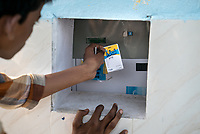 An iJal user uses the card to fill the water cans at the iJal station in Ambedkar Nagar in Medak, Telangana, India.