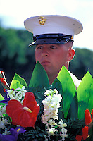 Soldier with flowers standing at Punchbowl Memorial on the Island of Oahu