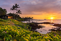 Sunset at Makaiwa Bay, with naupaka, tide pools, palm trees and a sailboat, Big Island.