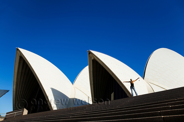 A woman stands atop the steps of the Sydney Opera House.  Sydney, New South Wales, AUSTRALIA.