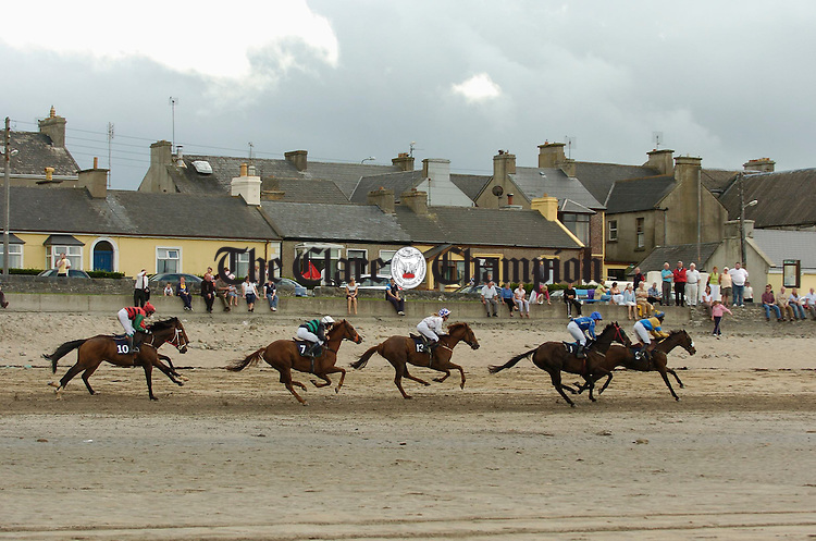 A race passes adjacent to the Strand Line of Kilkee during the annual Strand races. Photograph by John Kelly.