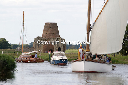 The Bishop of Norwich the Rev Graham James arrives by Wherry, a traditional Norfolk Broads sailing boat to take an interdenominational service at the ruined abbey of St Benets. Ludham Norfolk UK. Annually first Sunday in August.