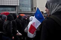 manifestanti incappucciati e bandiera francese