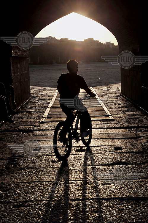 A boy rides a bicycle beneath the Khajoo Bridge. During recent years Iran has suffered a serious water shortage and the Zayandeh River has dried out.