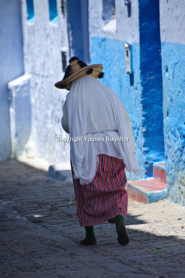 An elderly woman in traditional northern dress slowly makes her way in the mesmerizing blue streets of Chefchaouen (at the foot of the Rif mountains of Morocco) in the mesmerizing blue streets of Chefchaouen (at the foot of the Rif mountains of Morocco)