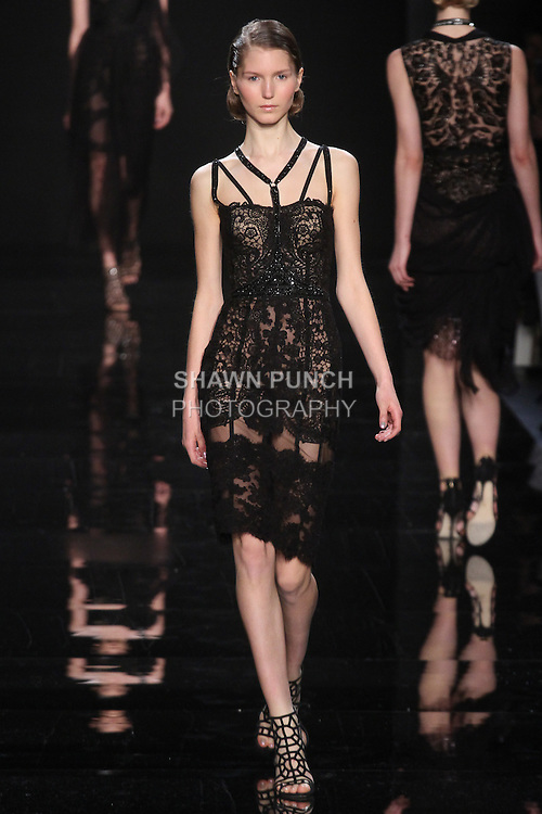 """Model walks runway in a black lace dress with jet black detail from the Reem Acra Fall 2016 """"The Secret World of The Femme Fatale"""" collection, at NYFW: The Shows Fall 2016, during New York Fashion Week Fall 2016."""
