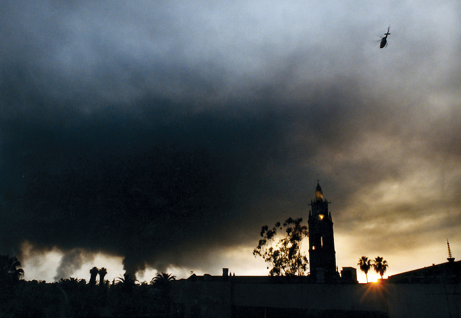 Los Angeles Times photo by Jim Mendenhall. The moment the curfew began at sunset on the third evening of the Los Angeles Riots. Smoke from major fires filled the sky. Reminds me of images from the middle east of oil fields burning during the first Gulf War.